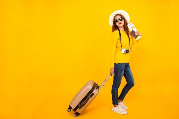 Volledig beeld, mooie reizigers aziatische die vrouw met camera en bagage op gele achtergrond wordt geïsoleerd.