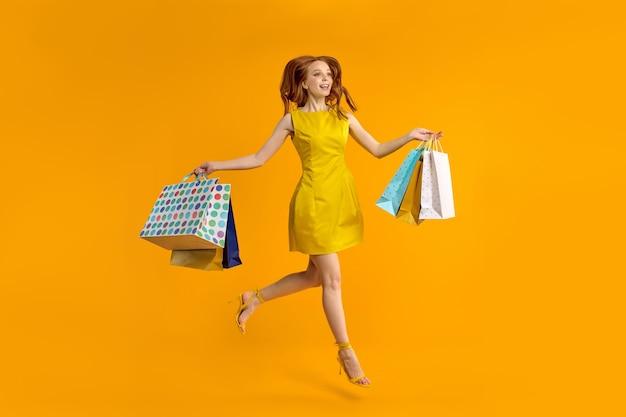 Volledig beeld van charmante jonge roodharige vrouw in gele jurk glimlachende blanke dame is auto...