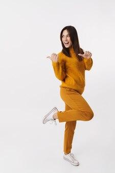 Volledig beeld van een mooie brunette volwassen vrouw die lacht en met de vinger opzij wijst naar copyspace geïsoleerd op wit