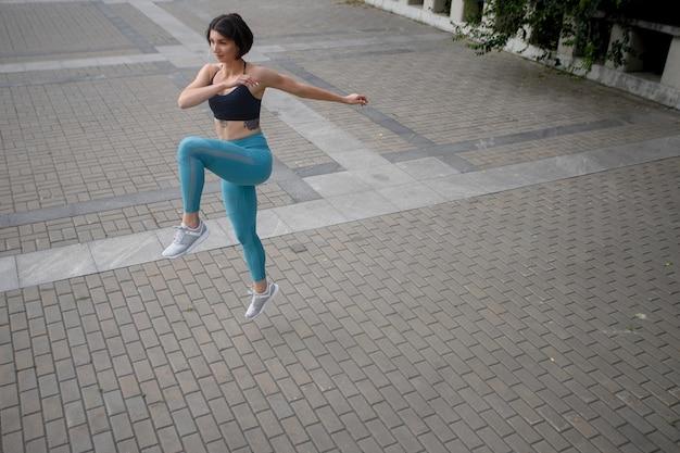 Volledig beeld van fitness meisje 20s in sportkleding die aan het trainen is en langs de muur rent