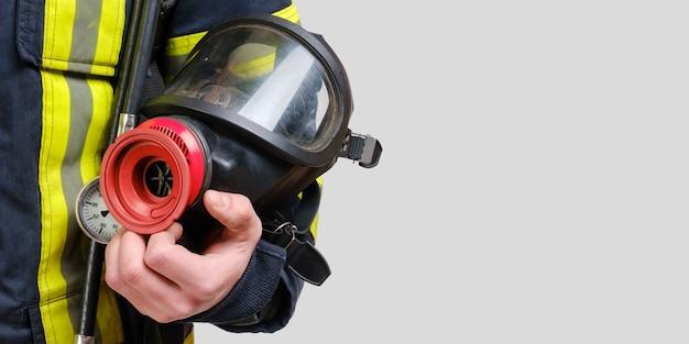 Volledig beschermend ademhalingsmasker in de hand van een niet-herkende brandweerman