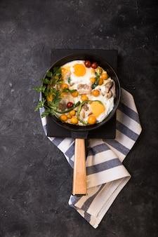 Volledig engels ontbijt gebakken ei, tomaat, spek, schotel in ijzeren koekenpan.