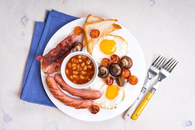 Volledig engels ontbijt met gebakken eieren, tomaten, worstjes, spek, champignons, toast en bonen