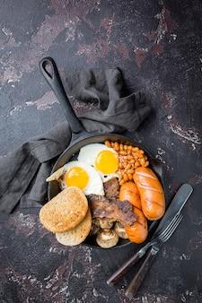 Volledig engels ontbijt met gebakken eieren, worstjes, spek, bonen, toast en tomaten op donkere steen
