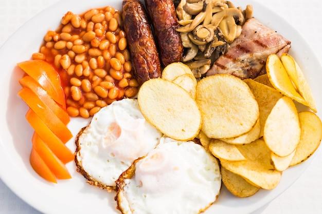 Volledig engels ontbijt met worstjes, tomaten en champignons, eieren, spek, gebakken bonen en chips.