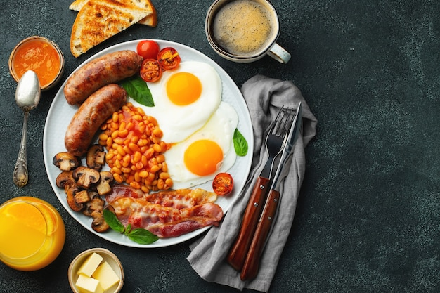 Volledig engels ontbijt op een bord met gebakken eieren, worstjes, spek, bonen, toast en koffie... bovenaanzicht.