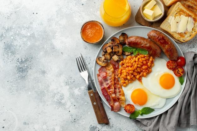 Volledig engels ontbijt op een bord met gebakken eieren