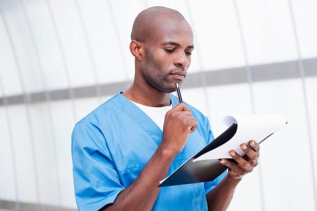 Volledig geconcentreerd aan het werk. doordachte jonge afrikaanse dokter in blauw uniform die klembord vasthoudt en ernaar kijkt terwijl hij zijn kin aanraakt met een pen