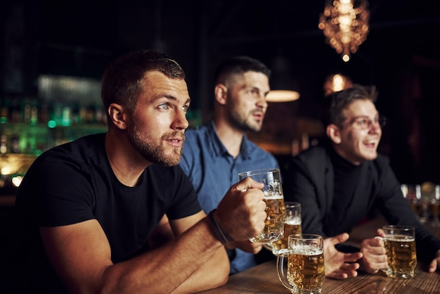 Volledig geconcentreerd. drie sportfans in een bar voetbal kijken. met bier in handen.