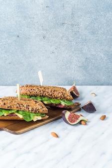 Volledig geladen hotdogs op hakbord met fig. plakken en amandelen over witte marmeren achtergrond