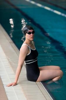 Volledig geschoten atleet aan de rand van het zwembad