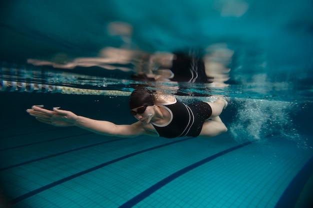 Volledig geschoten atleet met bril die onder water zwemt