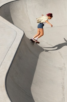 Volledig geschoten coole vrouw die plezier heeft op skateboard