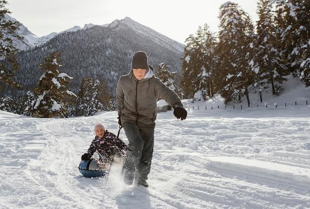 Volledig geschoten familieleden die in de sneeuw spelen