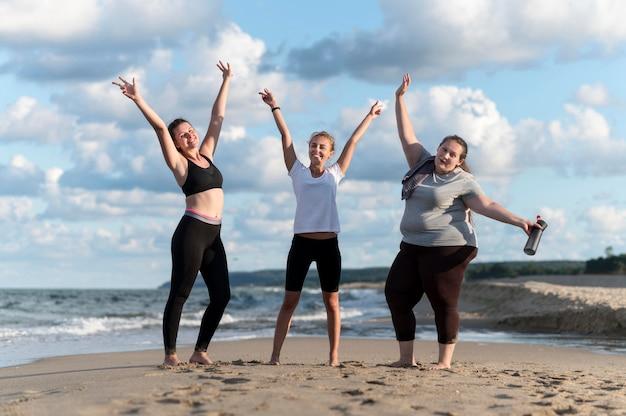 Volledig geschoten fitnessvrienden bij strand