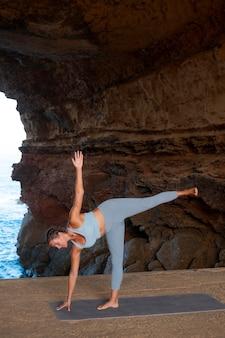 Volledig geschoten fitte vrouw die yoga doet