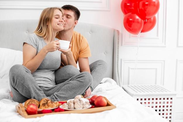 Volledig geschoten gelukkig paar met ontbijt in bed
