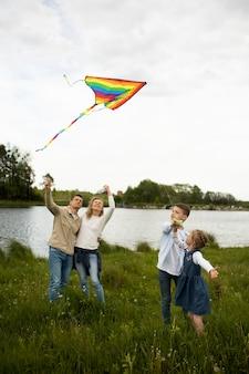 Volledig geschoten gelukkige familie die kleurrijke vlieger vliegt