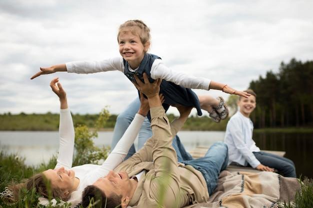 Volledig geschoten gelukkige familie die tijd doorbrengt in de natuur