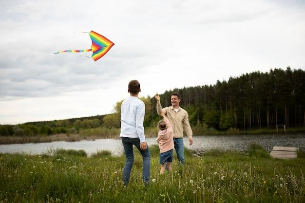 Volledig geschoten gelukkige familie vliegende vlieger buitenshuis