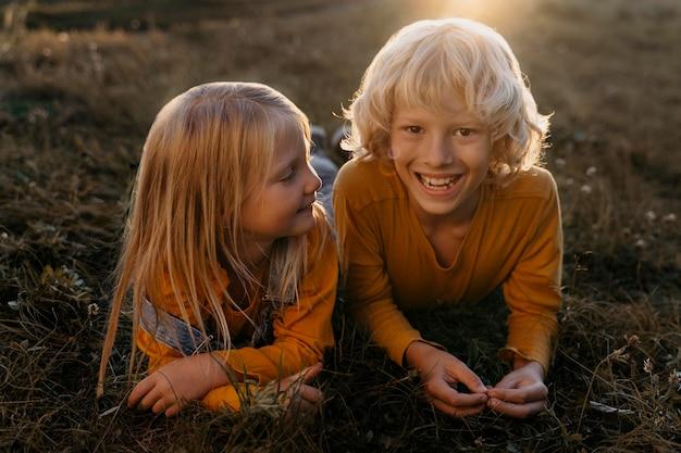Volledig geschoten gelukkige kinderen op gras
