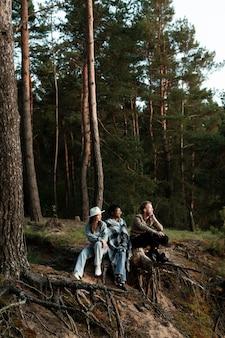 Volledig geschoten gelukkige mensen die in bos zitten