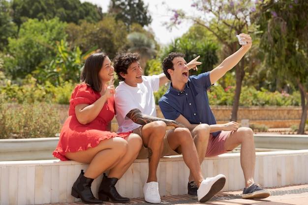 Volledig geschoten gelukkige vrienden die selfie nemen