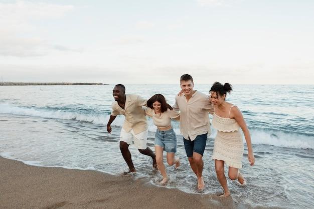Volledig geschoten gelukkige vrienden op het strand