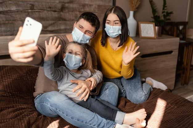 Volledig geschoten gezin dat maskers draagt