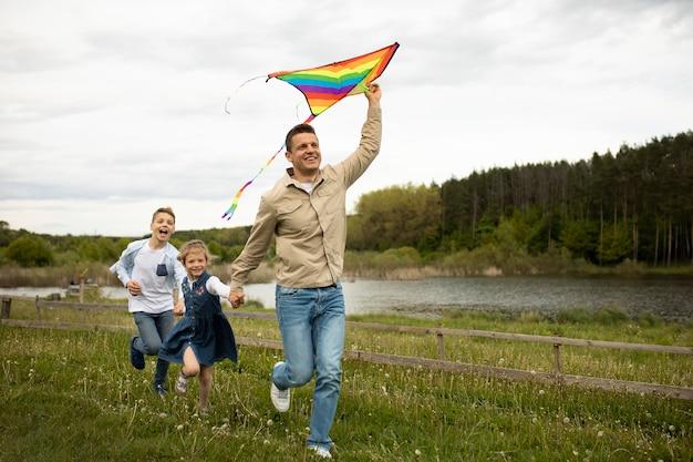 Volledig geschoten gezin met kleurrijke vlieger