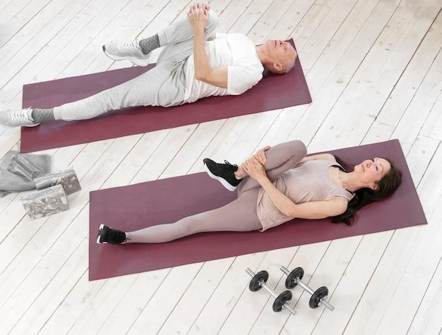 Volledig geschoten hogere mensen op yogamatten
