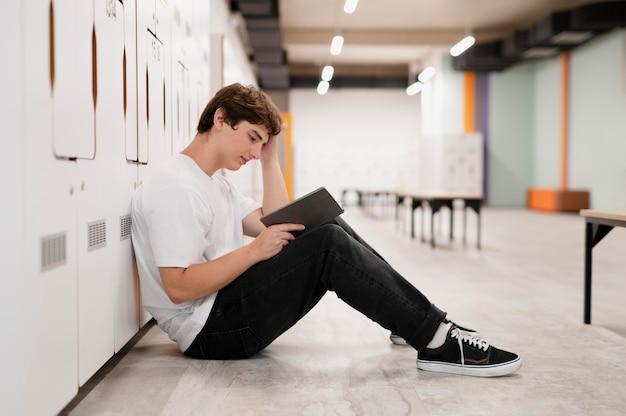 Volledig geschoten jongen die op de vloer op school leest