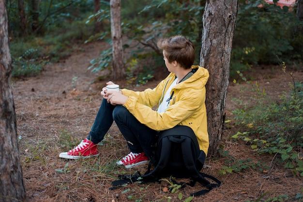 Volledig geschoten jongen zittend op de grond in de buurt van boom