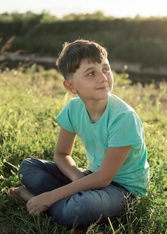 Volledig geschoten jongenszitting op gras