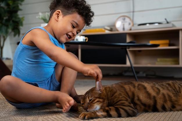 Volledig geschoten kind dat kat aanraakt