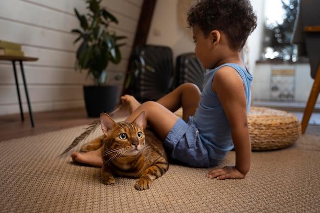 Volledig geschoten kind en kat op de vloer