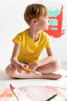 Volledig geschoten kind met penseel Gratis Foto