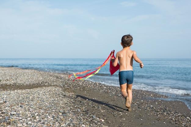 Volledig geschoten kind spelen met vlieger op het strand Gratis Foto