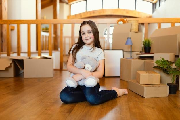 Volledig geschoten kind zittend op de vloer met speelgoed