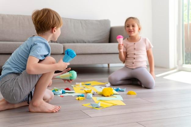 Volledig geschoten kinderen die met papier spelen