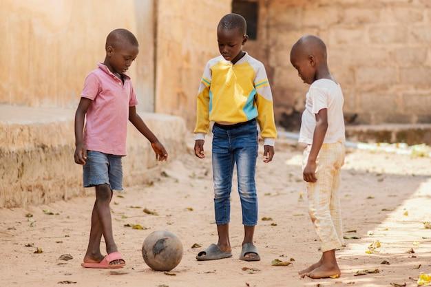 Volledig geschoten kinderen spelen met de bal