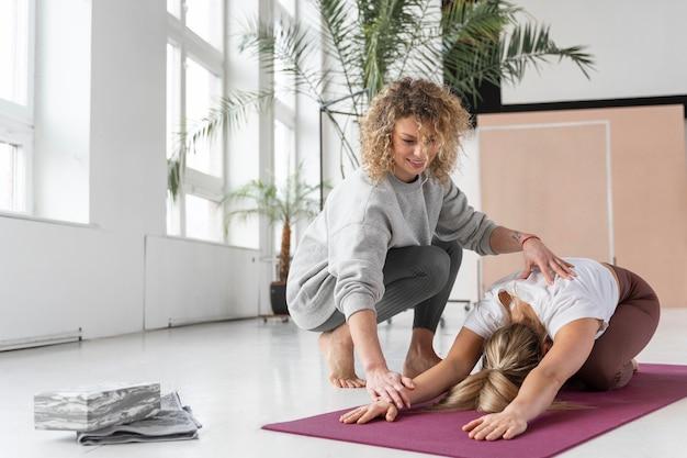 Volledig geschoten leraar die vrouw helpt yoga te doen