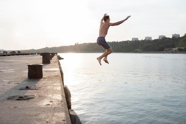 Volledig geschoten man die in het water springt