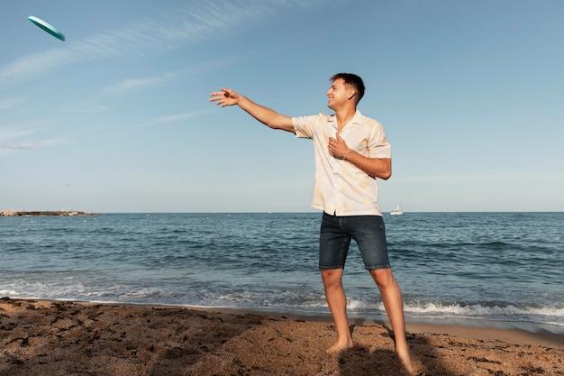 Volledig geschoten man die op het strand speelt