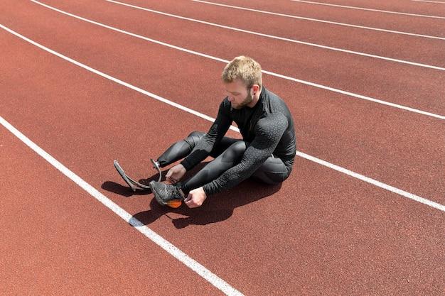 Volledig geschoten man die schoenveters bindt op de atletiekbaan