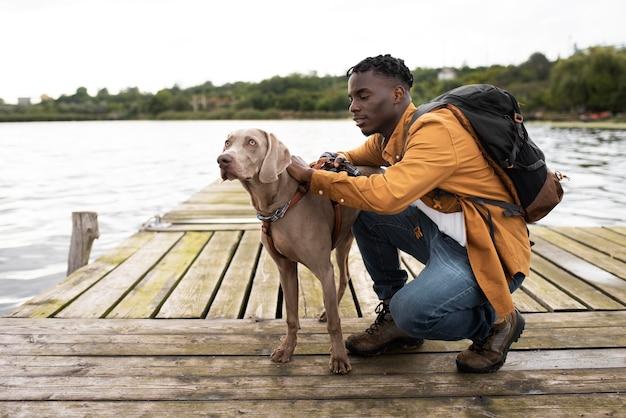Volledig geschoten man en schattige hond in de buurt van meer
