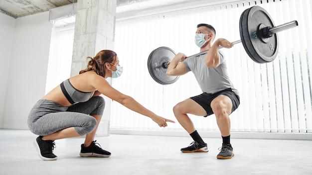 Volledig geschoten man en vrouw trainen met maskers