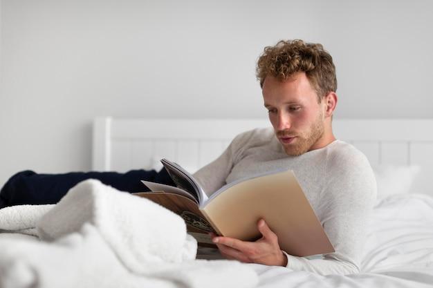 Volledig geschoten man leest boek in slaapkamer