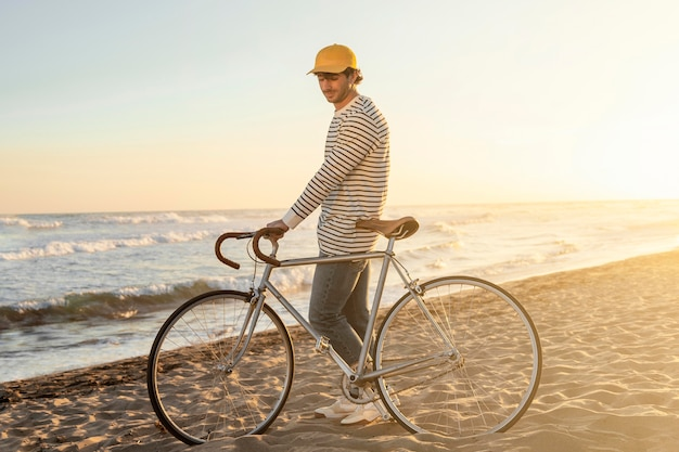 Volledig geschoten man met fiets aan zee