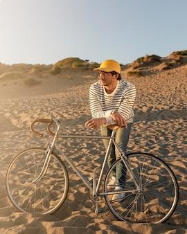 Volledig geschoten man met fiets op het strand